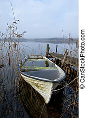 Waterfilled boat - Abandoned boat at lake an misty november...