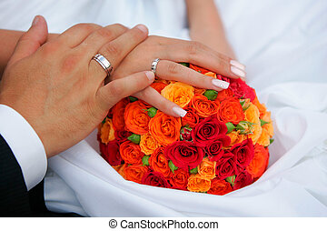 Newlywed couple holding hands over bouquet of flowers