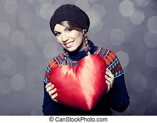 Lovely girl in sweater with toy heart.