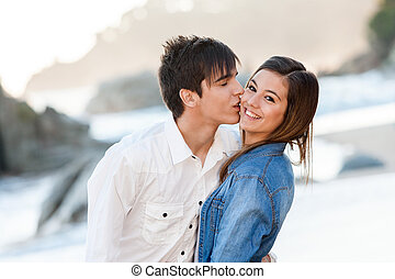 Cute teen couple in love on beach - Close up of handsome...