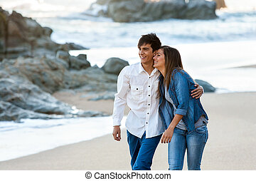 Cute teen couple walking along beach - Cute happy teen...