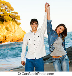 Happy couple raising arms at seaside - Portrait of happy...
