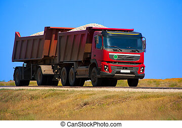 red dump truck with the trailer loaded with rubble