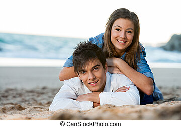 Young couple relaxing on beach at sunset - Close up of young...