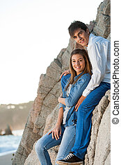 Young couple sitting on rocks at seaside - Full length...