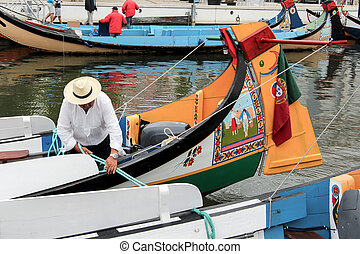 View daily work of portuguese sailor mooring traditional moliceiro boat, in a canal of Aveiro, Portugal