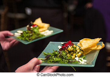Serving appetizers - Server holding a tray of appetizers at...