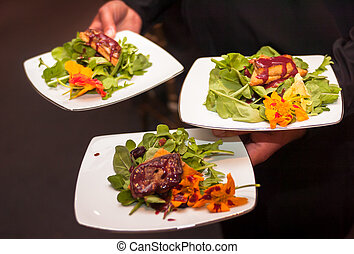 Serving entrees at a banquet - Server holding plated entrees...