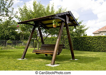 Swinging bench - Wooden swinging bench in the garden