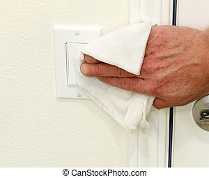 Cleaning a Light Switch - Hand cleaning a white home kitchen...