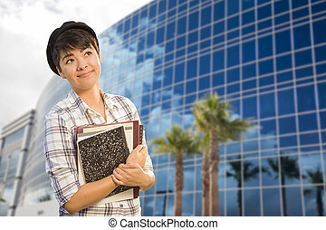 Mixed Race Female Student Holding Books in Front of Building