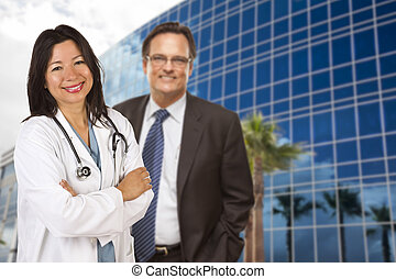 Hispanic Doctor or Nurse and Businessman in Front of Building