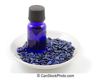 Essential oil and lapis lazuli gemstone on the plate