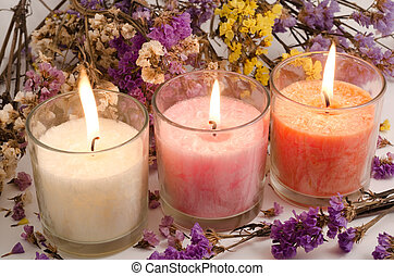 Candles and dried flowers - Three cup candles surrounded...