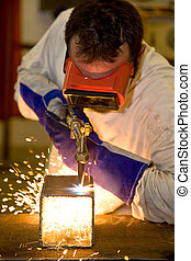 Welder Cutting with Flame - Welder using an acetylene torch...