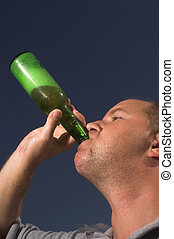 Man Drinking Beer - A man drinking a cold beer on a hot day