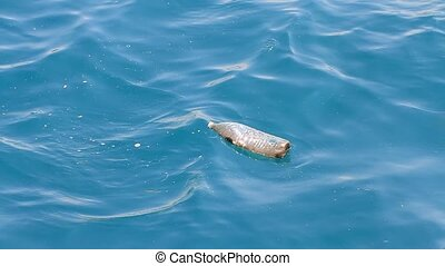 Used plastic bottle floating and polluting on water surface...