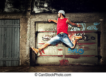 Young man jumping on grunge wall - Young man jumping dancing...