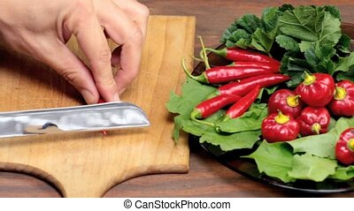 slicing red hot peppers - knife and red hot peppers on...