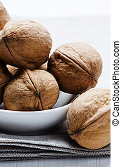 Walnuts in a plate on cloth close up