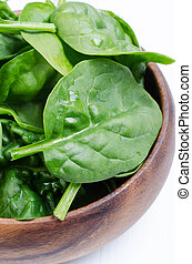 Fresh spinach in wooden bowl on white wooden table