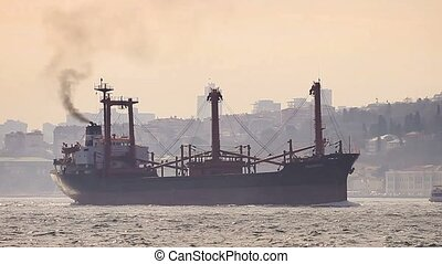 Marine air pollution - Istanbul in smog with a cargo ship