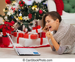 Happy woman with laptop near Christmas tree rejoicing...