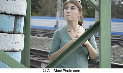 A young woman plays the fool on the railroad
