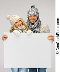 couple in a winter clothes holding blank board - picture of...