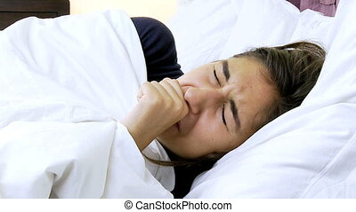 Sick woman coughing with flu - very sick young woman in bed...
