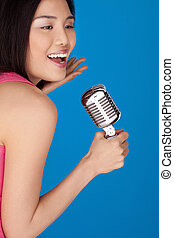 Laughing Asian woman with a microphone