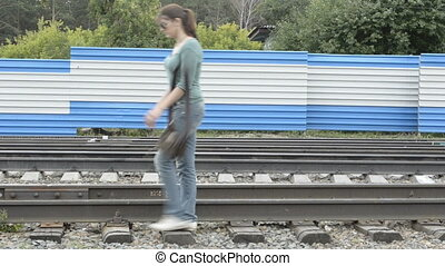 A young woman sit on the rails