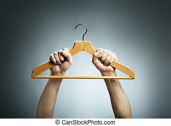 Old Hanger - Man holding an old wooden clothes hanger in his...