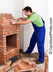 Worker building brick stove or fireplace