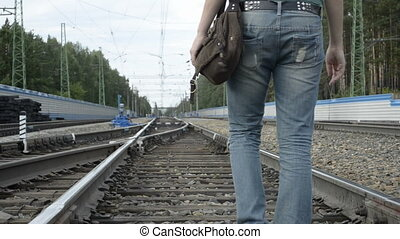 Tired young woman went off by railroad