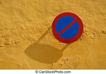 no parking sign on yellow wall background