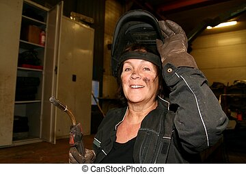 Female welder - Middle aged emale welder taking off her...