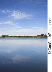 Fishing Boat On A Lake - A single fishing boat on a calm and...
