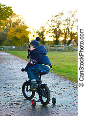 boy riding his bike through a countryside path