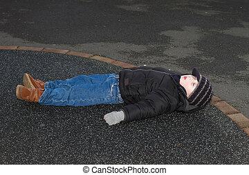 litte boy knocked down  outside on tarmac