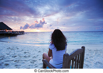 Woman sitting on beach chair at sunset