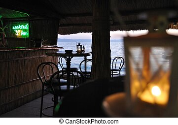 In the bar - Bar with chairs and tables with sea in...