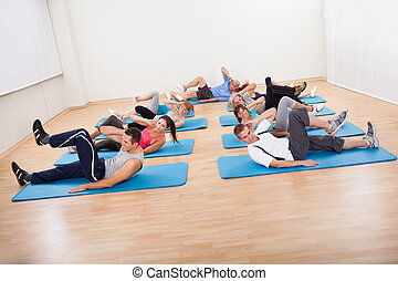Group of people exercising in a gym class - Large group of...