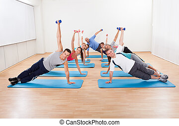 Large group of people working out in a gym balanced on one...