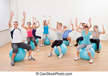 Large group of people doing pilates in a gym sitting on...