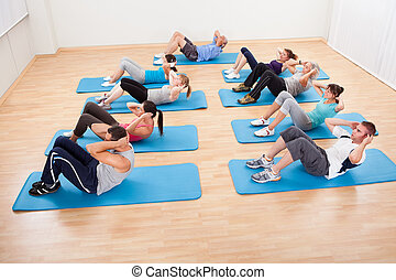 Group of people working out in a gym - Diverse group of...