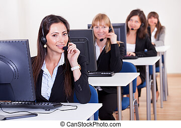Telephonists in a call centre - Row of attractive young...