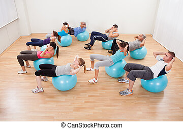 Class of diverse people doing pilates exercises in a gym...