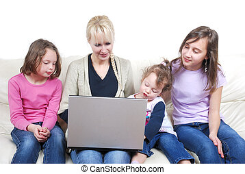 Family sitting on the sofa and using laptop