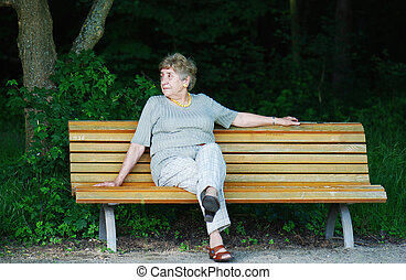 retiree sitting alone on park bench
